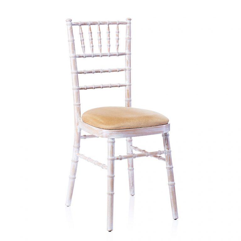 a limewash chiavari chair with an ivory seat pad