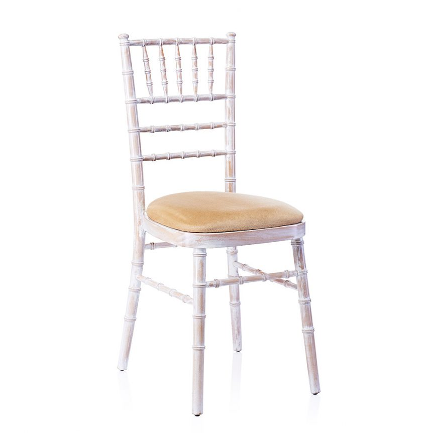 a limewash chiavari chair with an ivory seat pad