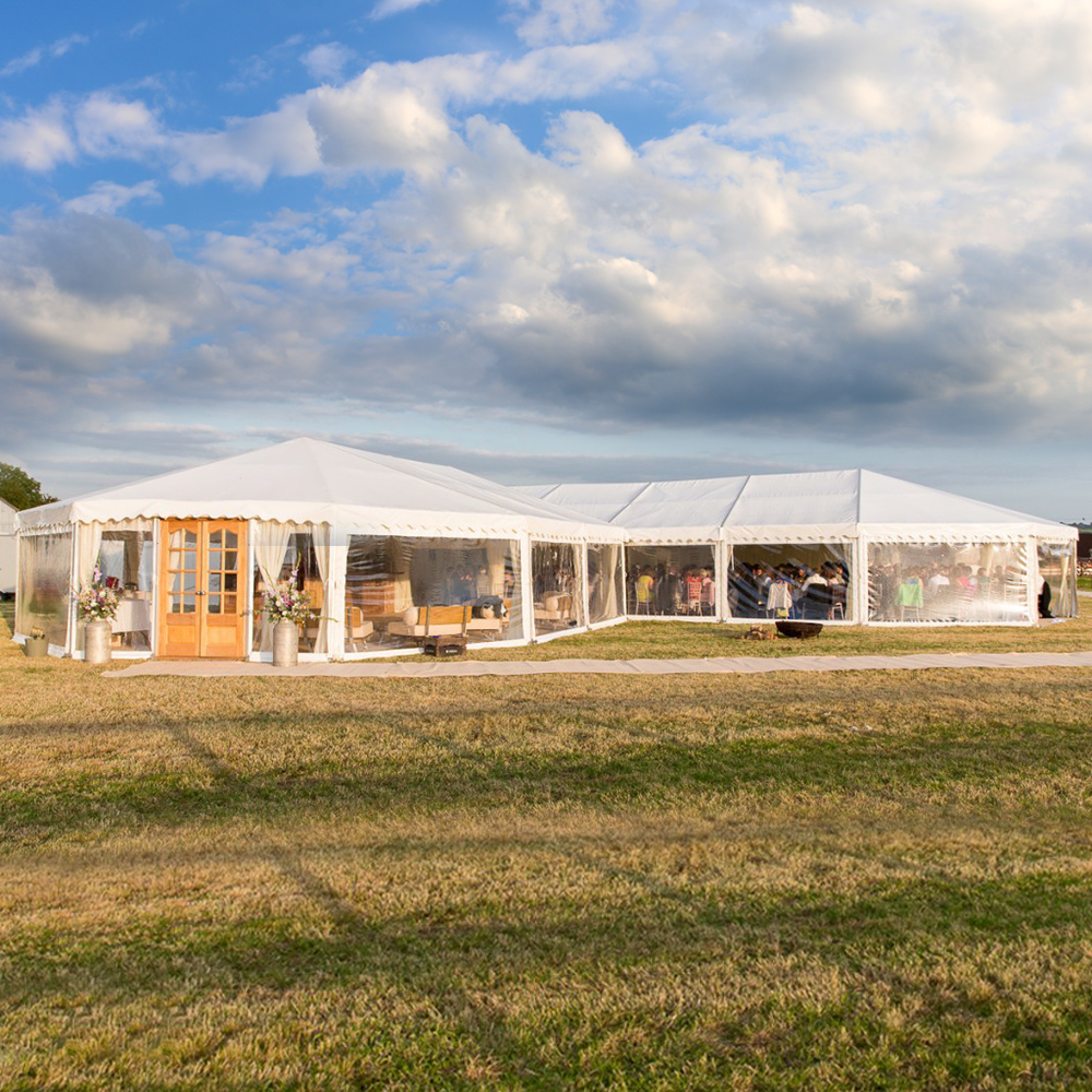 A marquee in a field on a sunny day in Dorset. Marquee hire dorset provided by Rochesters Event Hire