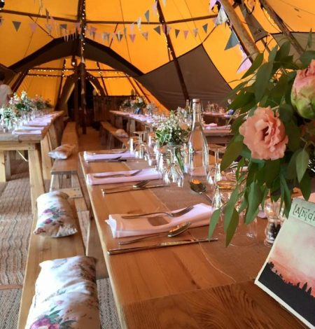 a rustic trestle table inside a tipi marquee for a wedding