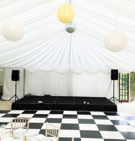 A black and white dancefloor and stage ready for a wedding in Dorset